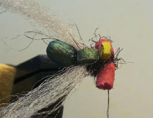 Predisporre un po' di dubbing di ICE DUB sul filo e incrociare attorno al cilindretto che formerà gli occhi. Se avete spazio per fare il nodo di chiusura in prossimità dell'occhiello, fatelo lì, altrimenti potete chiudere la mosca dietro agli occhi.
